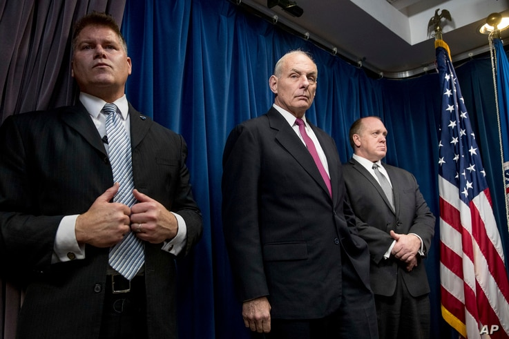 Homeland Security Secretary John Kelly, center, accompanied by U.S. Immigration and Customs Enforcement Acting Director Thomas Homan, right, and a member of his security detail, attends a news conference at the U.S. Customs and Border Protection head...