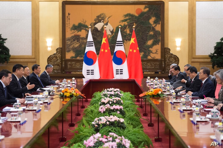 South Korean President Moon Jae-in, second right, and Chinese President Xi Jinping, second left, are seen with other officials during a bilateral meeting at the Great Hall of the People in Beijing, China, Dec. 14, 2017.