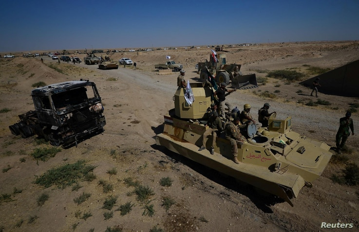 Iraqi army members and Shi'ite Popular Mobilization Forces (PMF) gather in Al-Al-Fateha military airport south of Hawija, Iraq, Oct. 2, 2017.