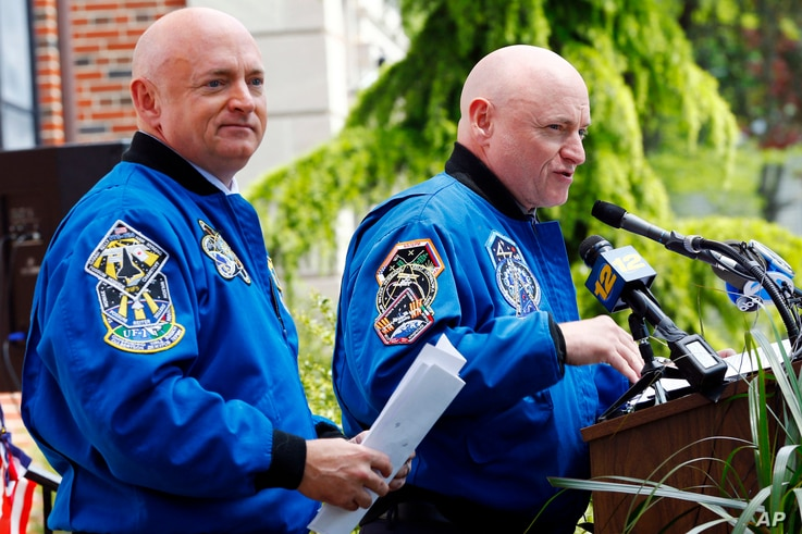 FILE - Retired astronaut Scott Kelly, right, speaks while standing next to his astronaut twin brother, Mark Kelly, during an event renaming the elementary school they attended, May 19, 2016, in West Orange, N.J.