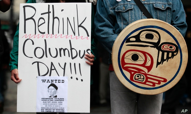 FILE - Demonstrators stand during a Native American protest against Columbus Day.