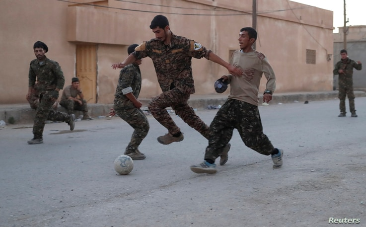 Kurdish fighters from the People's Protection Units (YPG) play football on a street in Raqqa, Syria, June 26, 2017.