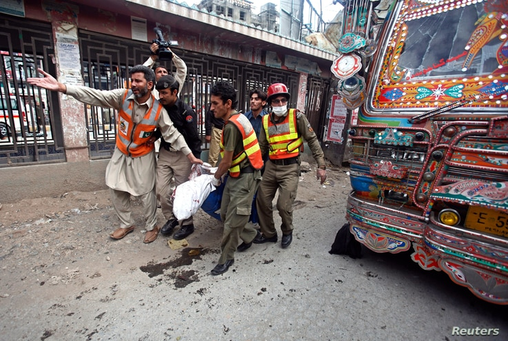 Rescue workers carry a dead body away from the site of a blast at University Road in Peshawar April  29, 2013.