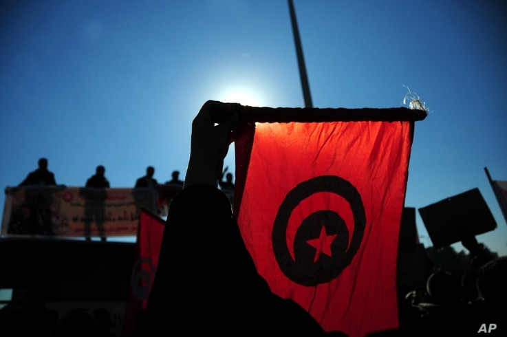 FILE - Tunisian police officers wave the national flag and posters as they demonstrate outside the presidential palace in Carthage near Tunis, Tunisia, to demand a pay increase, Jan. 25, 2016.