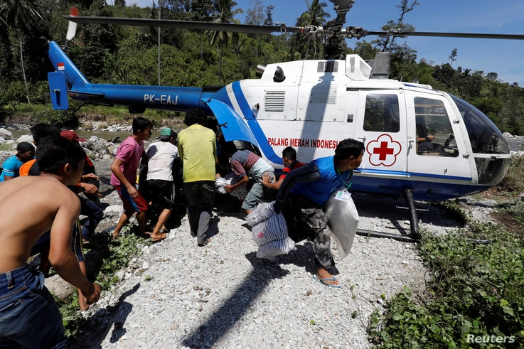 Villagers affected by the earthquake rush an Indonesian Red Cross helicopter carrying aid in Biromaru, Sigi Regency, south of Palu, Central Sulawesi, Indonesia, Oct. 5,  2018.