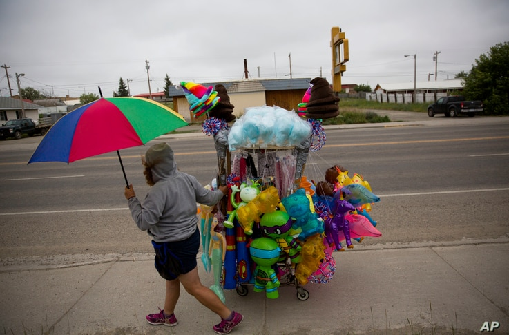 A vendor wheels her cart of souvenirs before the start of the North American Indian Days parade on the Blackfeet Indian Reservation in Browning, Mont., Saturday, July 14, 2018
