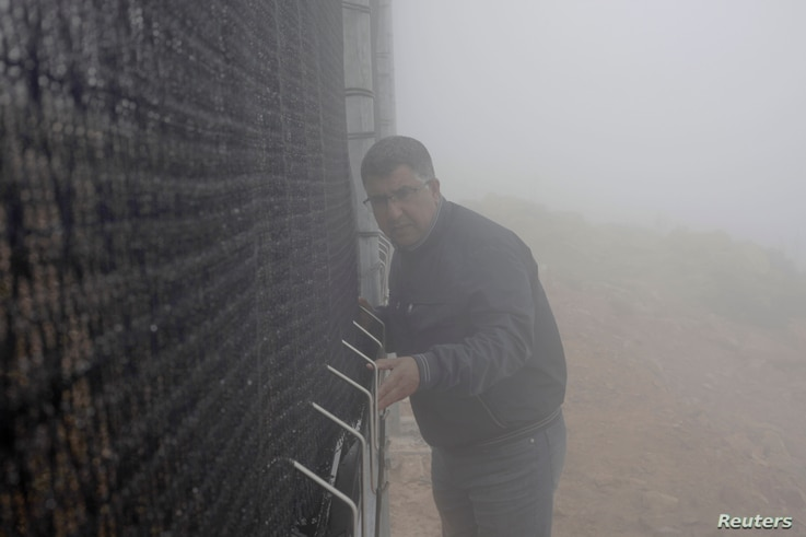 Mounir Abbar, fog manager for Dar Si Hmad, tends to the fog collection nets on Mount Boutmezguida, Morocco, Feb. 21, 2018.