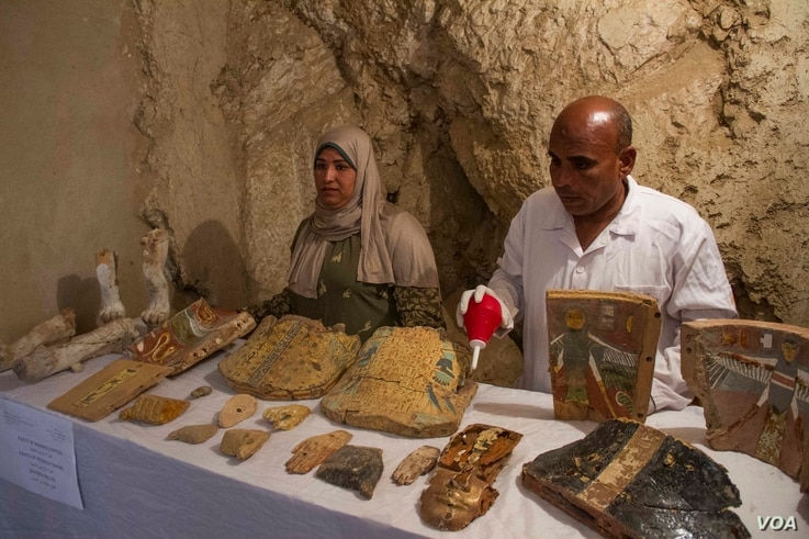 Egyptian excavation workers restore funeral furniture found in a newly discovered tomb, Kampp 161, in the Draa Abul Naga necropolis on Luxor's West Bank, Egypt, Dec. 9, 2017. (H. Elrasam/VOA)