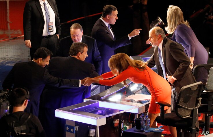 Bobby Jindal, left, Chris Christie, Mike Huckabee and Rick Santorum talk to moderators Trish Regan, Gerald Seib and Sandra Smith, right, after a Republican presidential debate at Milwaukee Theatre, Tuesday, Nov. 10, 2015, in Milwaukee.