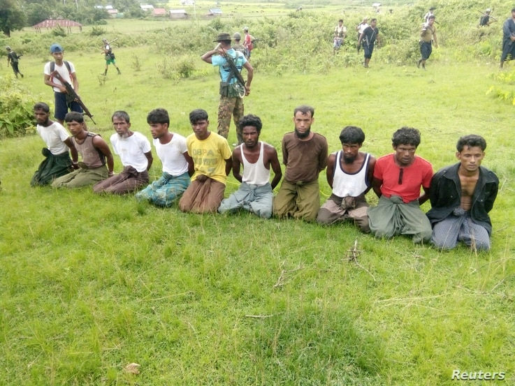 FILE - Ten Rohingya Muslim men with their hands bound kneel as members of the Myanmar security forces stand guard in Inn Din village, Sept. 2, 2017.