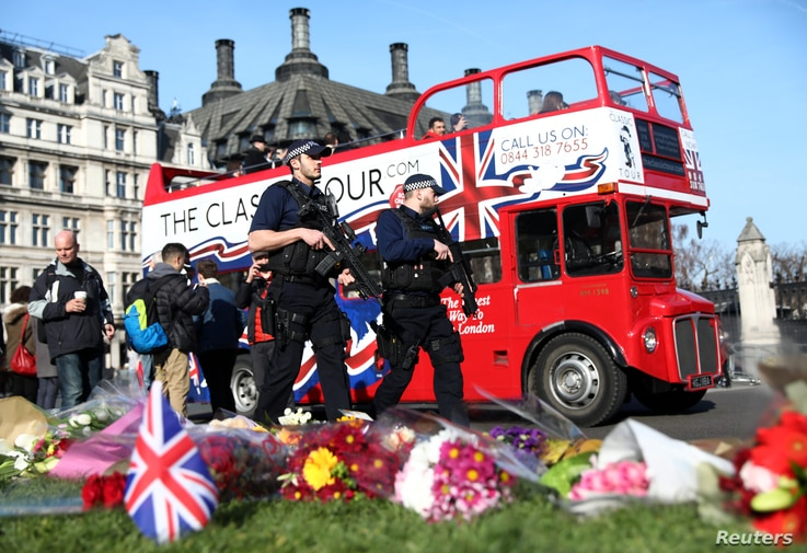 Armed police officers pass tributes in Parliament Square following a recent attack in Westminster, London, Britain, March 24, 2017.