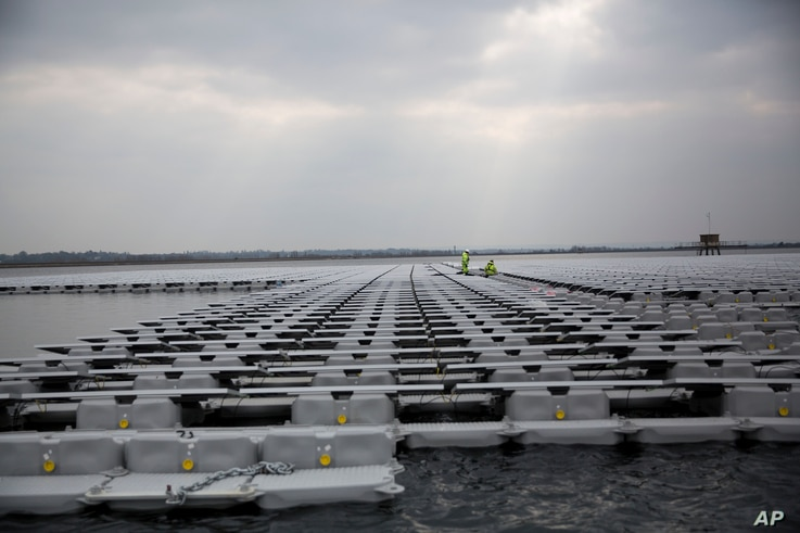 FILE - Contractors work on a floating solar panel array on the Queen Elizabeth II Reservoir near Walton-on-Thames in southwest London, March 21, 2016. Britain's unique climate is seen as having contributed to its reaching its current capacity of rene...