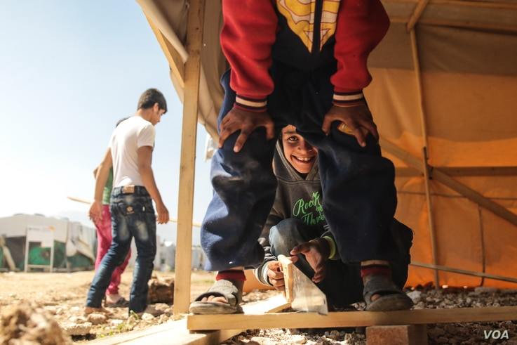 A young Syrian boy helps out his family's efforts to rebuild a shelter in the camp they have just moved to.