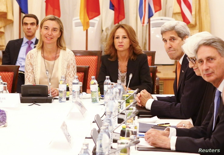 European Union foreign policy chief Federica Mogherini, left, U.S. Secretary of State John Kerry, third from left, Under Secretary for Political Affairs Wendy Sherman and British Foreign Secretary Philip Hammond, right, wait for the start of a meetin...
