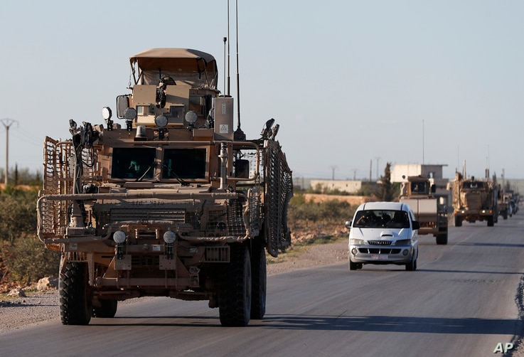 FILE - A convoy of U.S. troops drive along a road with local allied fighters, in Manbij, northern Syria, March 31, 2018.