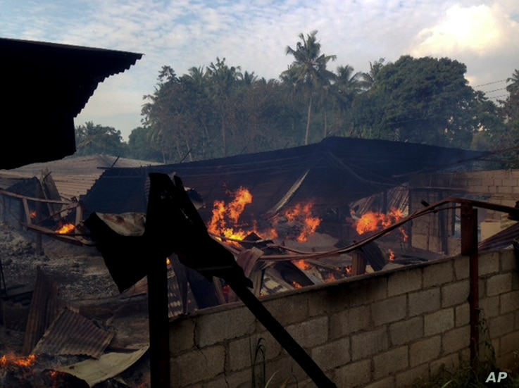 A timber depot burns in Mullegama village in Kandy, Sri Lanka, Wednesday, March. 7, 2018.