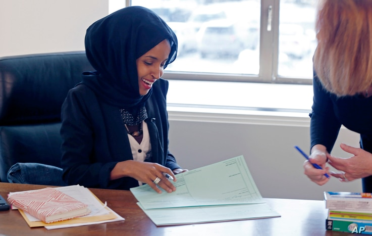 FILE - New State Rep. Ilhan Omar (L) confers with another lawmaker in her office two days after the 2017 Legislature convened in St. Paul, Minn.