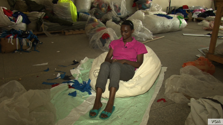 Lilian Wairimu sits on a beanbag she made for a client. It takes at least six days to make each item. (M. Yusuf/VOA)
