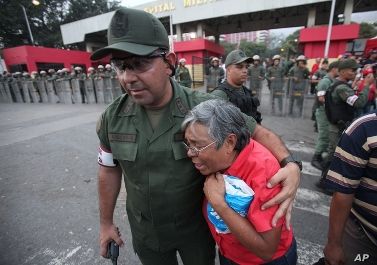 An army officer comforts a supporter of President Hugo Chavez outside the military hospital in Caracas, Venezuela, March 5, 2013.