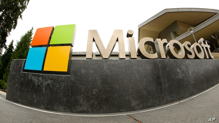 FILE - Tthe Microsoft Corp. logo appears outside the Microsoft Visitor Center in Redmond, Washington, July 3, 2014. In a lawsuit filed April 14, 2016, Microsoft is suing the US government over a federal law that lets authorities examine customers' em