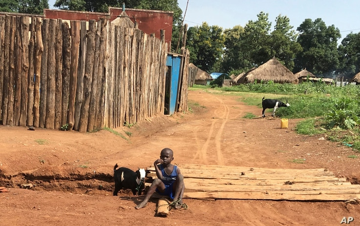 FILE - A young boy sits on the road in the town of Yei on July 13. 2017, one of the few remaining residents in a city riddled with murder, rape and abductions.