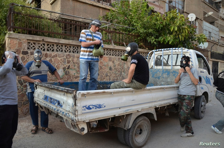 Activists wear gas masks as they look for dead bodies and collect samples to check for chemical weapon use in Zamalka, Damascus, August 22, 2013.