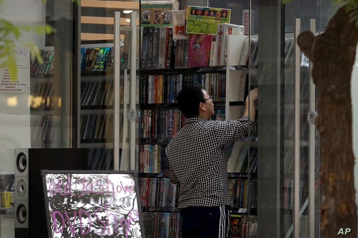FILE - A man shops at a store selling DVDs and CDs in Beijing, April 27, 2016. China has been one of several countries targeted by U.S. officials for leaving American producers of music, movies and other copyrighted material open to rampant piracy.