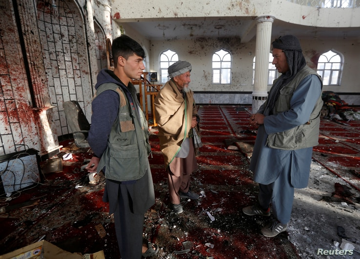 Afghan men inspect inside a Shi'ite Muslim mosque after a suicide attack in Kabul, Afghanistan October 21, 2017.