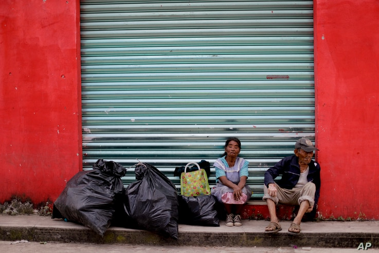 A couple sits with their belongings on the sidewalk, in front of a closed shop in Tepeojuma, Mexico, Sept. 24, 2017.