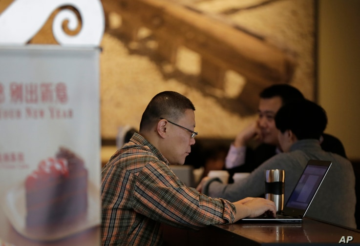 FILE - In this Feb. 16, 2015 file photo, a man surfs Internet on his laptop computer at a Starbuck cafe in Beijing. Chinese President Xi Jinping called Wednesday, Dec. 16 for governments to cooperate in regulating Internet use, stepping up efforts to...