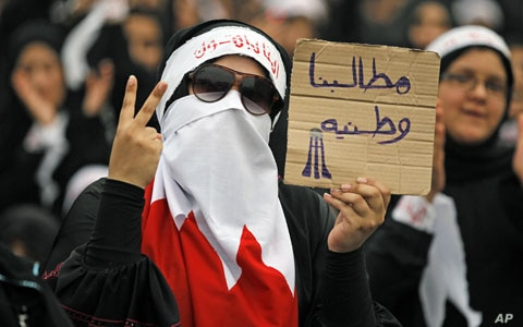 """A Bahraini female Shi'ite protester holds a sign reading: """"our demands are for country"""" during a rally in the village of Diraz, West of Manam, July 1, 2011"""