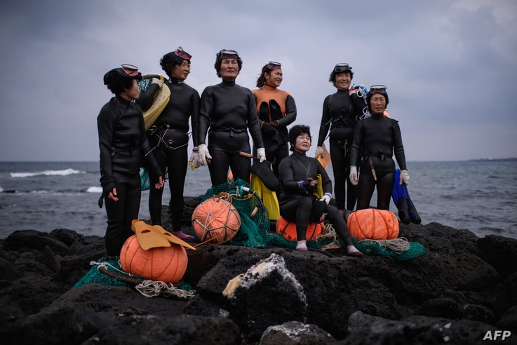 FILE - A group of haenyeo pose for photographers as they perform a demonstration during a media event organized by the Foreign Press Center, on South Korea's southern island of Jeju, Nov. 6, 2015. The term haenyeo, or sea women, refers to women who u...