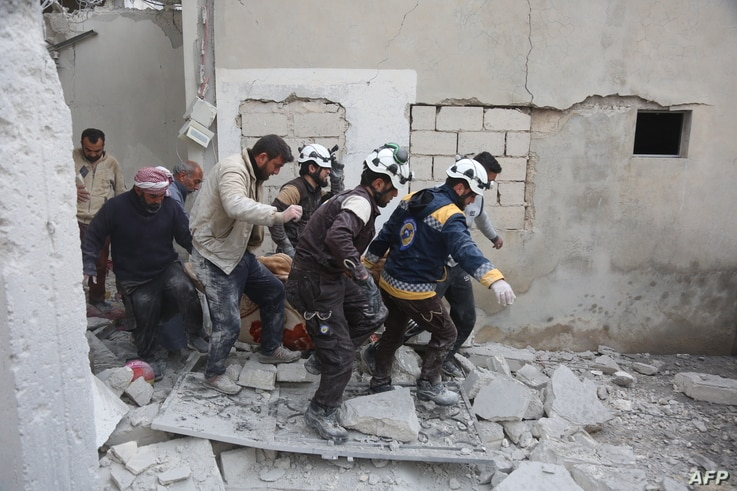 """Members of the Syrian Civil Defence (also known as """"The White Helmet"""") carry a wounded person following reported shelling in the town of Khan Sheikhun in the southern countryside of the rebel-held Idlib province, Feb. 26, 2019."""