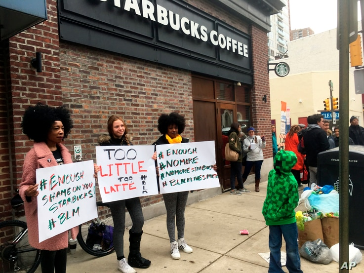 Protesters gather outside a Starbucks in Philadelphia, April 15, 2018, where two black men were arrested Thursday after Starbucks employees called police to say the men were trespassing.