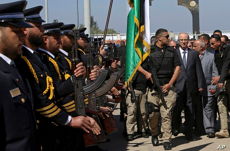 Palestinian Prime Minister Rami Hamdallah walks behind a bodyguard as he receives an honor guard on his arrival to the opening ceremony for a long-awaited sewage plant project east of Jebaliya, in the northern Gaza strip, March 13, 2018.
