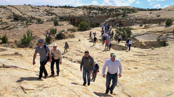 FILE - Utah state legislators and their staff lead the way for Interior Secretary Ryan Zinke, Utah Gov. Gary Herbert and others in the distance, May 8, 2017.