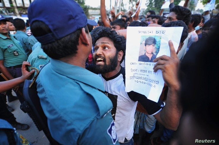 A relative argues with a member of the police as he shows a picture of a garment worker, who has been missing, during a protest demanding capital punishment for those responsible for the collapse of the Rana Plaza building in Savar, outside Dhaka, Ap