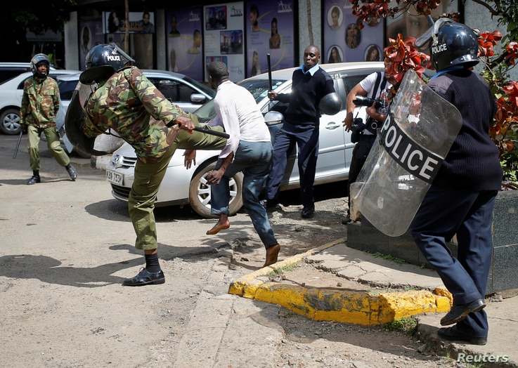 Kenyan policemen beat a protester during clashes in Nairobi, May 16, 2016.