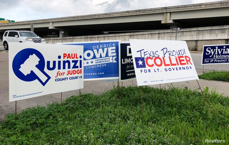 Political campaign signs stand outside a polling station in Austin, Texas, March 5, 2018, ahead of the first statewide U.S. primary of the year.
