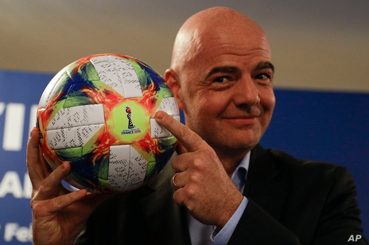 FIFA President Gianni Infantino holds the official ball of the upcoming Women's Soccer World Championship as he poses for photographers during a press conference at the end of an executive committee meeting in Rome, Feb. 27, 2019.
