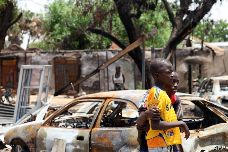Two boys stand in front of burnt cars in Michika, a city recaptured from Boko Haram by the Nigeria military early this year, May 10, 2015.
