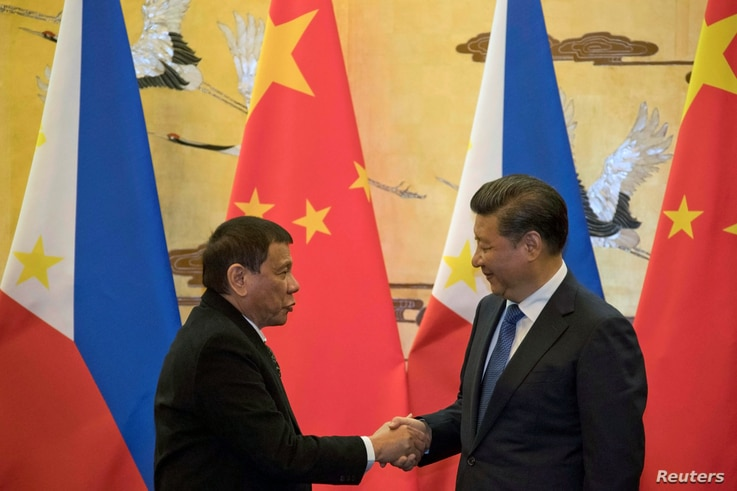 FILE - Philippine President Rodrigo Duterte (L) and Chinese President Xi Jinping shake hands after a signing ceremony held in Beijing, Oct.  20, 2016.