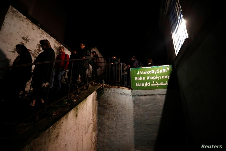A group of Hungarians who take part in an organized tour to learn about Budapest's Muslim community walk out from a small mosque at an apartment building in Budapest, Hungary, Nov. 3, 2017.