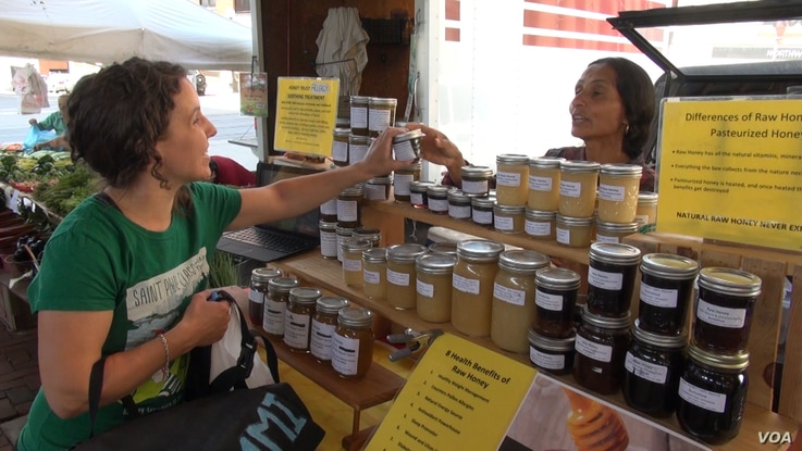 Immigrants have been a large part of the market's resurgence in the last 30 years. Originally from Nepal, Susan Dahl sells honey. (J. Soh/VOA)