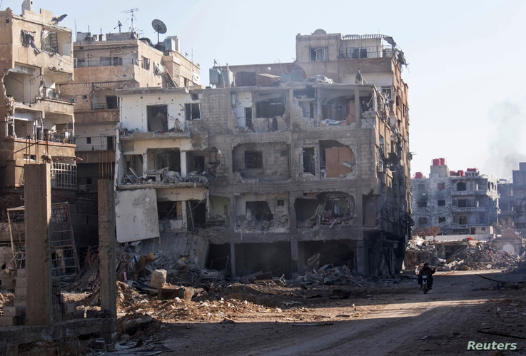 Men ride a motorbike past buildings damaged by what activists said was shelling by forces loyal to Syria's President Bashar al-Assad in Daraya, Jan. 15, 2014.