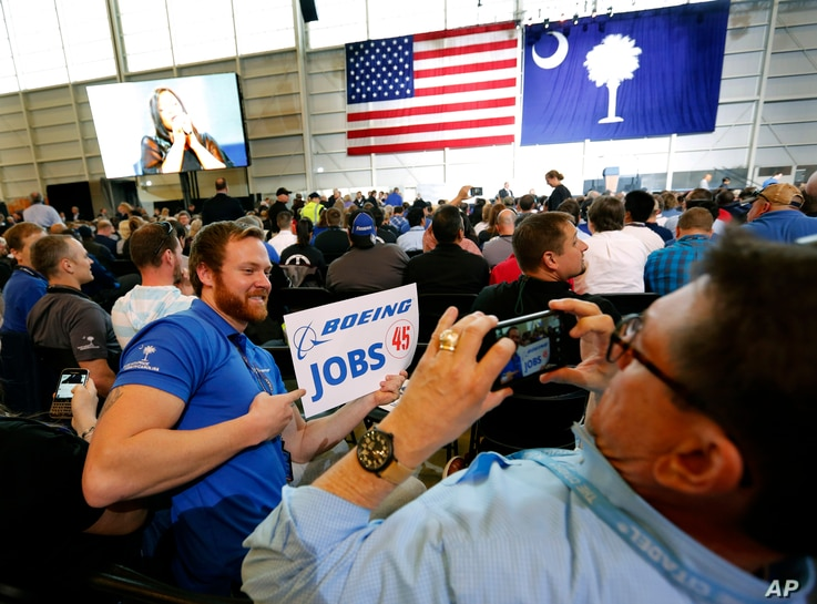 Patrick Brothers, left, smiles for the camera as Wendell Bailey, takes his photo as the two Boeing employees wait with others for President Donald Trump to speak, Feb. 17, 2017, in the final assembly building at Boeing South Carolina in North Charles...