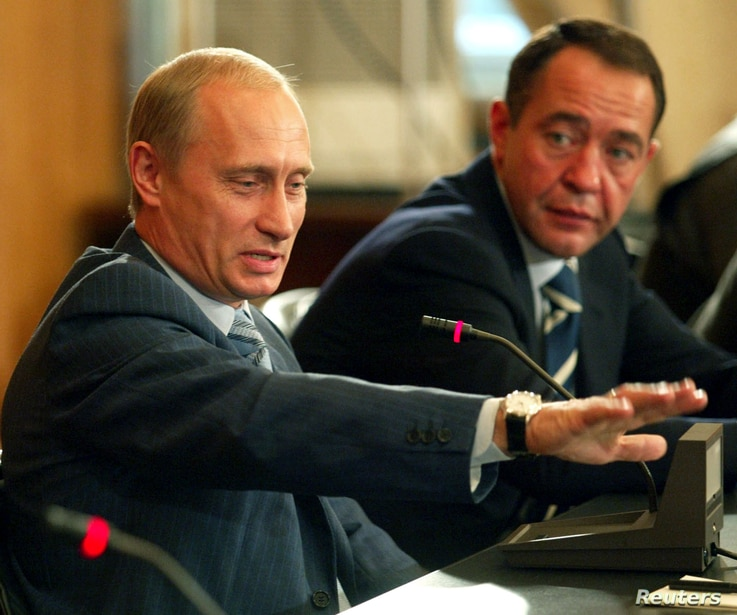 FILE - Russian President Vladimir Putin (L) and Mikhail Lesin, Russian press minister at the time, are seen during a meeting in Vladivostok, Russia, Aug. 24, 2002. Lesin, once considered a close associate of Putin, was found dead with blunt-force inj...