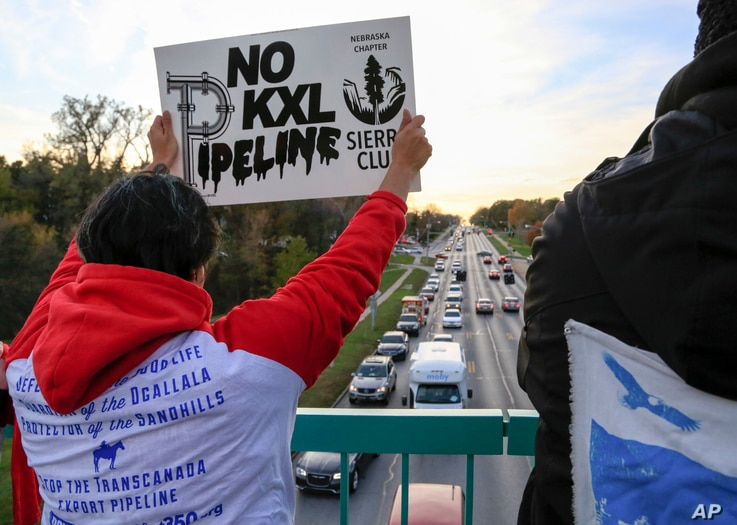 Opponents of the Keystone XL pipeline demonstrate on the Dodge Street pedestrian bridge during rush hour in Omaha, Neb., Nov. 1, 2017. The Nebraska Public Service Commission has until Nov. 23 to decide whether to approve or reject a proposed state ro...
