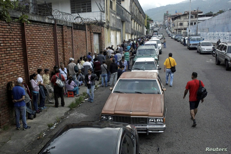 People line up outside a supermarket next to motorists queuing for gas near a gas station of the Venezuelan state-owned oil company PDVSA in San Cristobal, Venezuela, Nov. 10, 2018.