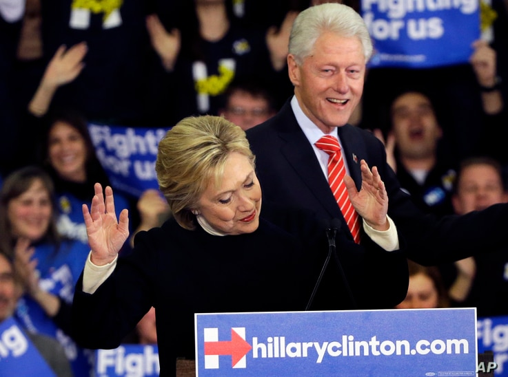 Democratic presidential candidate Hillary Clinton reacts as former President Bill Clinton smiles at her New Hampshire presidential primary campaign rally in Hooksett, New Hampshire, Feb. 9, 2016.